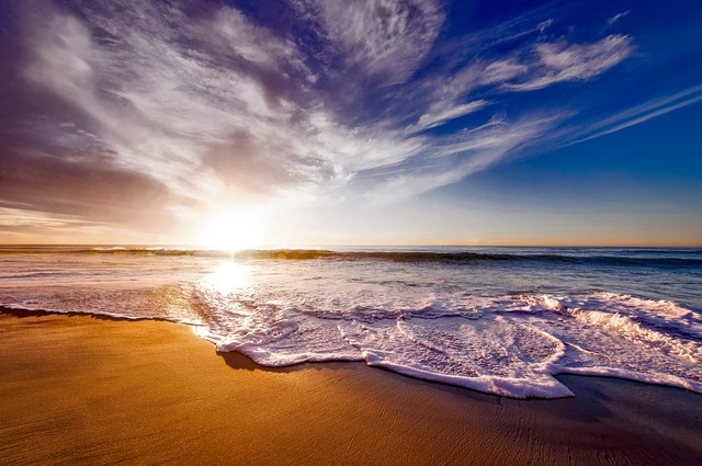 seashore-under-white-and-blue-sky-during-sunset